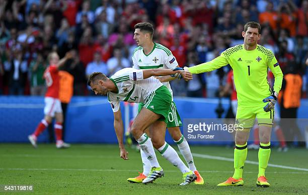 Northern Ireland goalkeeper Michael McGovern consoles own goal scorer Gareth McAuley during the Round of 16 UEFA Euro 2016 match between Wales and...