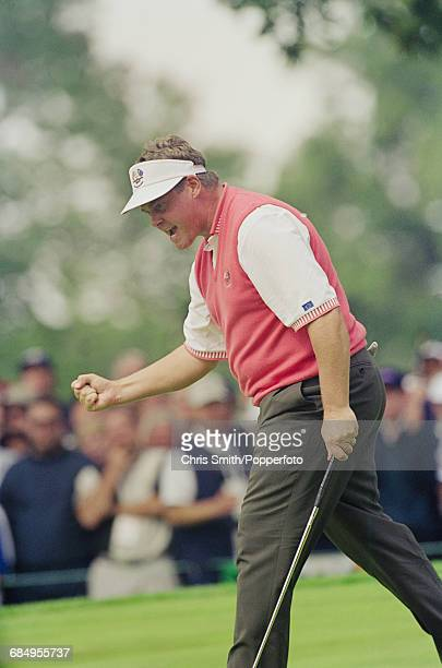 Northern Ireland golfer Darren Clarke pictured celebrating after sinking a successful putt on a green for Team Europe during play to lose to Team USA...