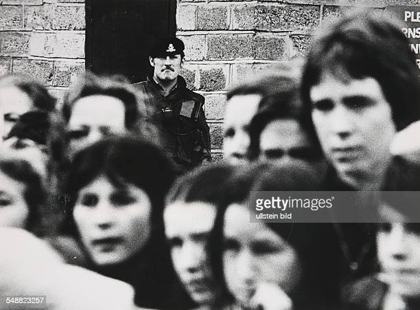 Northern Ireland, Londonderry: A member of the Duke of Wellington regiment stationed in the city keeps an eye on a crowd of young people entering the...