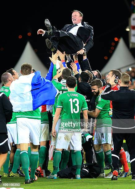 Northern Ireland players throw Northern Ireland manager Michael O'Neill up in the air as they celebrate victory and qualification after the UEFA EURO...