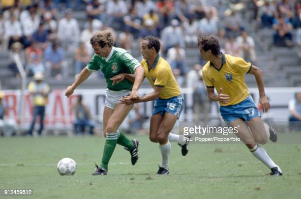 Northern Ireland striker Gerry Armstrong is challenged by Elzo of Brazil with Branco looking on during the FIFA World Cup match between Northern...