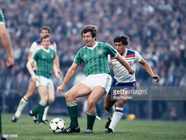 Northern Ireland striker Gerry Armstrong is challenged by England defender Kenny Sansom during the British Championship match at Windsor Park in...