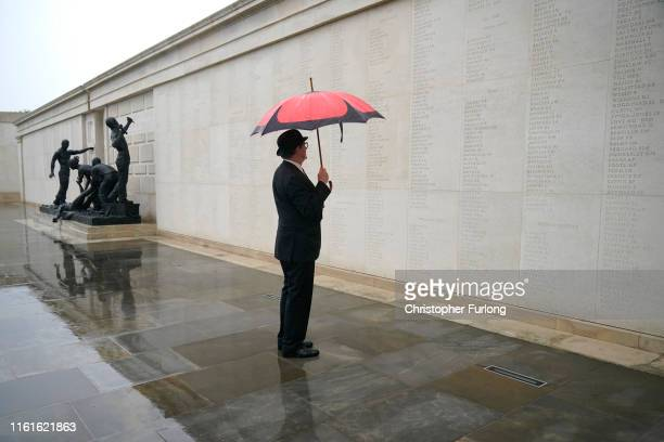 Northern Ireland veteran with a poppy umbrella reads the names of the fallen at The National Memorial Arboretum on August 14, 2019 in Stafford,...