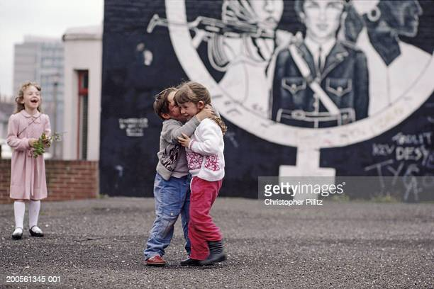 Northern Ireland, west Belfast, children playing in front of buildings with murals