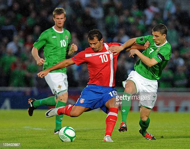 Northern Ireland's Chris Baird vies with Dejan Stankovic of Serbia during the Euro 2012 Group C qualifying football match between Northern Ireland...