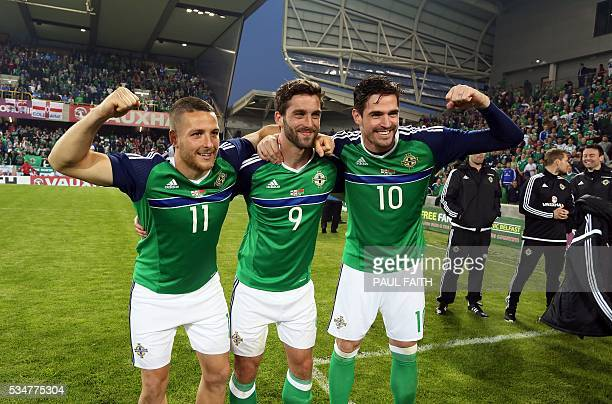 Northern Ireland's Conor Washington Will Gregg and Kyle Lafferty who scored the three goals celebrate after beating Belarus 30 during an...
