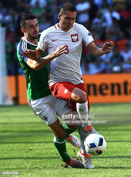 Northern Ireland's defender Conor McLaughlin vies with Poland's defender Artur Jedrzejczyk during the Euro 2016 group C football match between Poland...