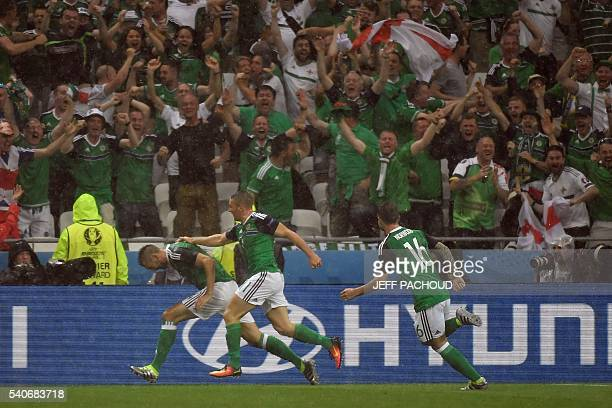 Northern Ireland's defender Gareth McAuley celebrates with Northern Ireland's forward Conor Washington and Northern Ireland's midfielder Oliver...