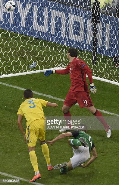 Northern Ireland's defender Gareth McAuley scores against Ukraine's goalkeeper Andriy Pyatov during the Euro 2016 group C football match between...