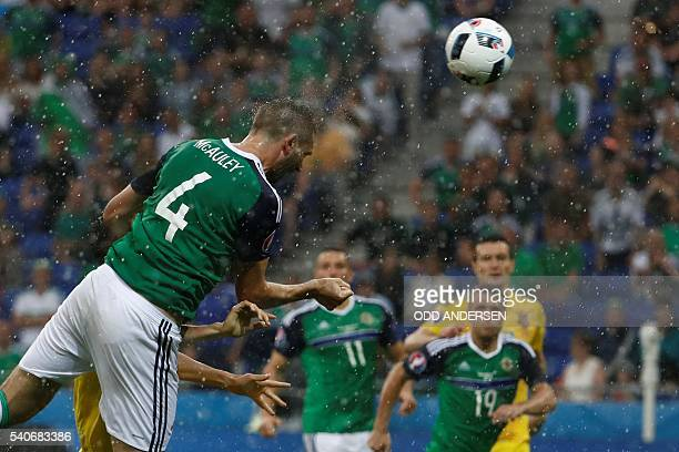 TOPSHOT Northern Ireland's defender Gareth McAuley scores the opening goal during the Euro 2016 group C football match between Ukraine and Northern...