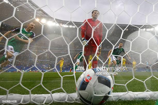 TOPSHOT Northern Ireland's defender Jonny Evans celebrates the opening goal scored by Northern Ireland's defender Gareth McAuley past Ukraine's...