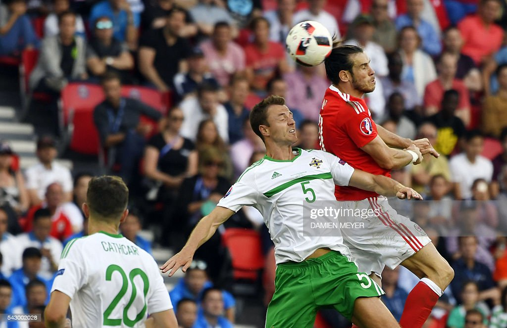 Northern Ireland's defender Jonny Evans (C) vies for the ball with Wales' forward Gareth Bale during the Euro 2016 round of sixteen football match Wales vs Northern Ireland, on June 25, 2016 at the Parc des Princes stadium in Paris. / AFP / DAMIEN