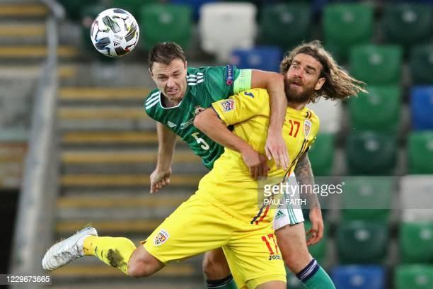 Northern Ireland's defender Jonny Evans vies with Romania's midfielder Eric Bicfalvi during the UEFA Nations League group b1 football match between...