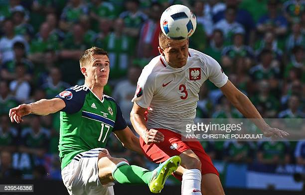 Northern Ireland's defender Paddy McNair vies with Poland's defender Artur Jedrzejczyk during the Euro 2016 group C football match between Poland and...