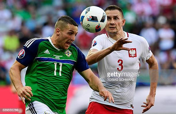 Northern Ireland's forward Conor Washington vies with Poland's defender Artur Jedrzejczyk during the Euro 2016 group C football match between Poland...