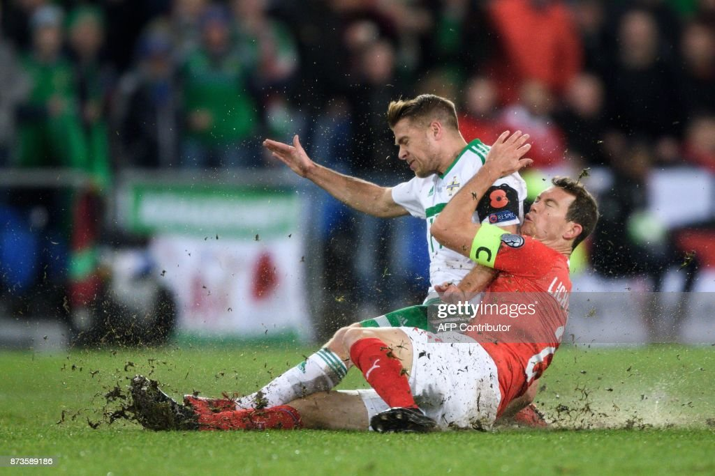 TOPSHOT - Northern Ireland's forward Jamie Ward (L) and Swiss midfielder Stephan Lichtsteiner vie for the ball during the FIFA 2018 World Cup play-off second leg qualifying football match between Switzerland and Northern Ireland at St Jakob-Park Stadium in Basel on November 12, 2017. / AFP PHOTO / Fabrice COFFRINI