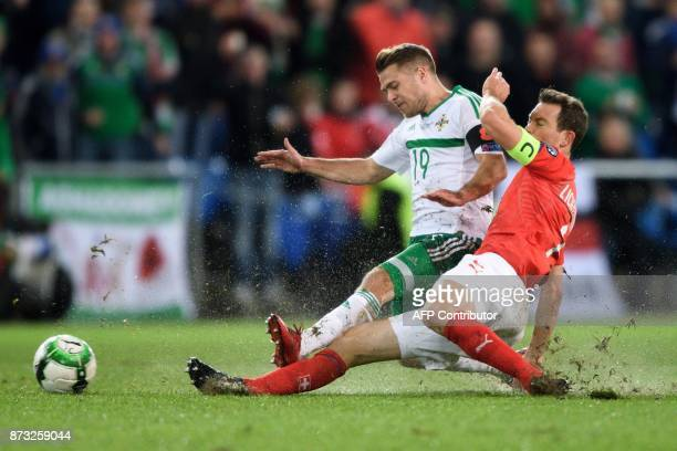 Northern Ireland's forward Jamie Ward vies with Swiss midfielder Stephan Lichtsteiner during the FIFA 2018 World Cup playoff second leg football...