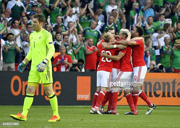 Northern Ireland's goalkeeper Michael McGovern walks away as Wales palyers celebrate their 1-0 win during the Euro 2016 round of sixteen football...