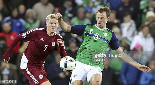 Northern Ireland's Jonny Evans vies for the ball against Latvia's striker Artjoms Rudnevs during the international friendly football match between...