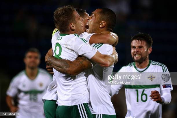 Northern Ireland's midfielder Josh Magennis celebrates with teammates after scoring during the 2018 FIFA World Cup qualifying football match San...