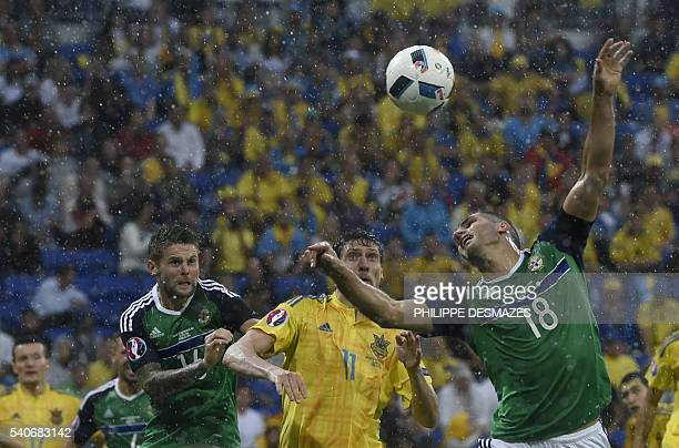 TOPSHOT Northern Ireland's midfielder Oliver Norwood and Northern Ireland's defender Aaron Hughes vie with Ukraine's forward Yevhen Seleznyov during...