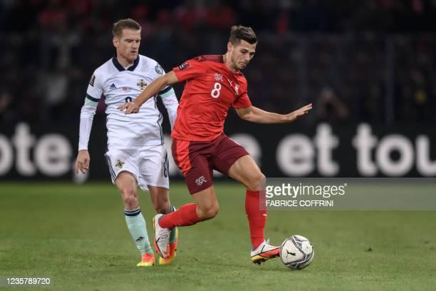 Northern Ireland's midfielder Steven Davis and Switzerland's midfielder Remo Freuler vie for the ball during the FIFA World Cup 2022 Group C...