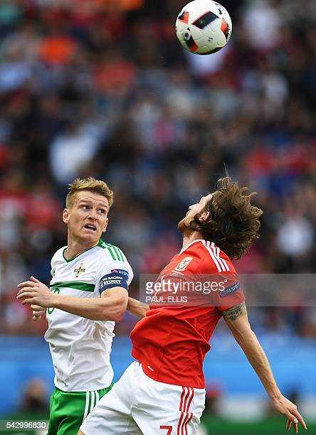 Northern Ireland's midfielder Steven Davis vies for the header with Wales' midfielder Joe Allen during the Euro 2016 round of sixteen football match...