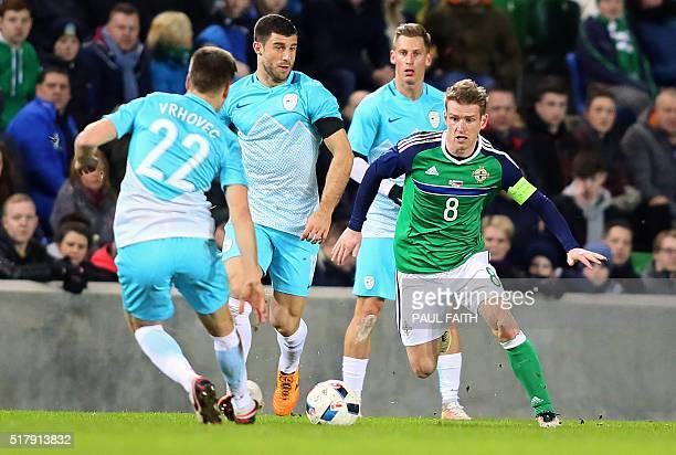 Northern Ireland's midfielder Steven Davis vies with Slovenia's midfielder Blaz Vrhovec during the international friendly football match between...