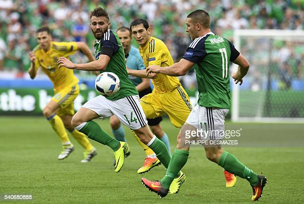 TOPSHOT Northern Ireland's midfielder Stuart Dallas and Northern Ireland's forward Conor Washington run with the ball during the Euro 2016 group C...