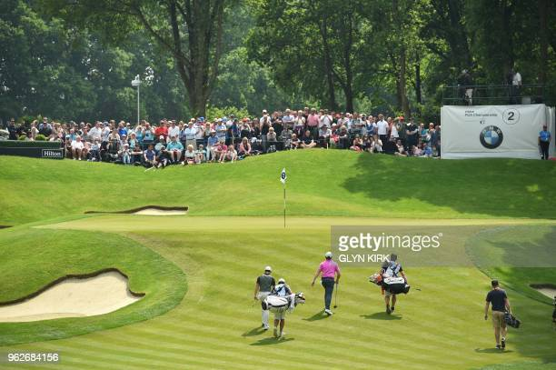 Northern Ireland's Rory McIlroy and England's Sam Horsfield walk onto the second green on day three of the golf PGA Championship at Wentworth Golf...