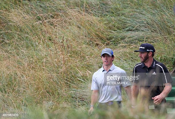 Northern Ireland's Rory McIlroy and US golfer Dustin Johnson walk from a tee on day three of the 2014 British Open Golf Championship at Royal...
