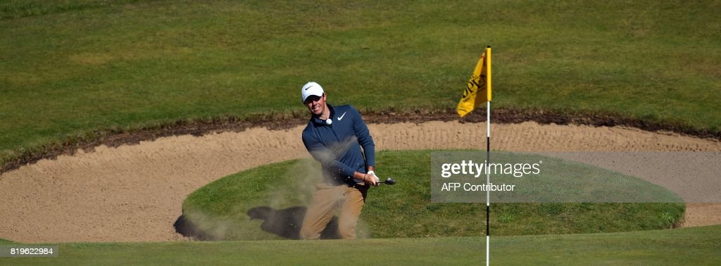 Northern Ireland's Rory McIlroy chips out of a bunker on the 7th hole during his opening round on the first day of the Open Golf Championship at Royal Birkdale golf course near Southport in north west England on July 20, 2017. / AFP PHOTO / Ben STANSALL / RESTRICTED