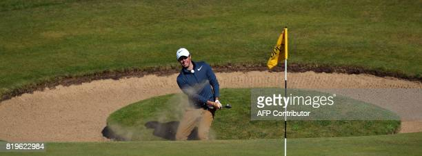 Northern Ireland's Rory McIlroy chips out of a bunker on the 7th hole during his opening round on the first day of the Open Golf Championship at...