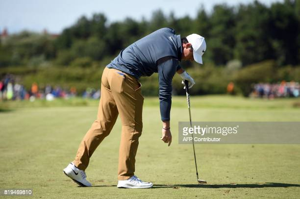 Northern Ireland's Rory McIlroy reacts after hitting into a bunker at the par 3 4th hole during his opening round on the first day of the Open Golf...