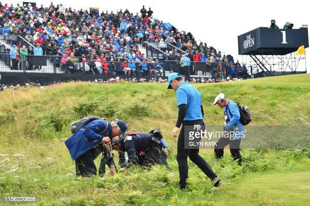 Northern Ireland's Rory McIlroy searches for his ball at the first hole during the first round of the British Open golf Championships at Royal...