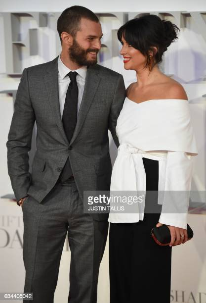 Northern Irish actor Jamie Dornan and his wife English actress Amelia Warner pose on the red carpet upon arrival at the UK premiere of Fifty Shades...