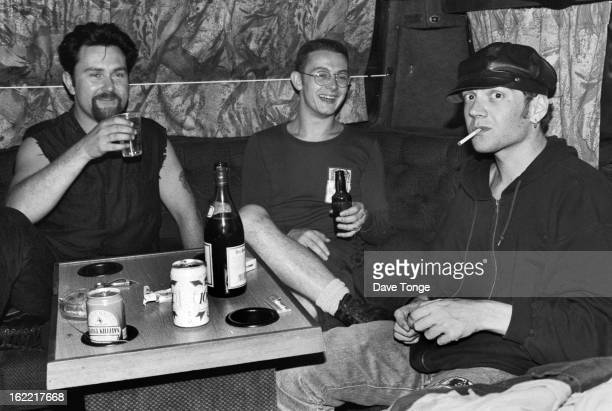Northern Irish alternative rock band Therapy sit at a table drinking on a tour bus UK circa 1993 Left to right Andy Cairns Michael McKeegan and Fyfe...