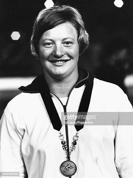 Northern Irish athlete Mary Peters smiles as she wears her silver medal for the shot put event at the Commonwealth Games in Kingston, Jamaica, August...