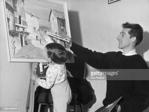 Northern Irish footballer and amateur artist Ken Hamilton assisted by his two-year-old son Gary as he works on a painting at his home in...