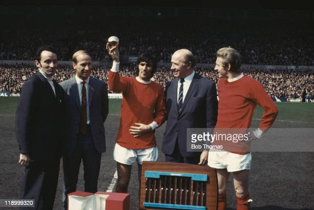 Northern Irish footballer George Best holds up his 1968 Footballer Of The Year award as Bobby Charlton Denis Law and manager Matt Busby look on 19th...