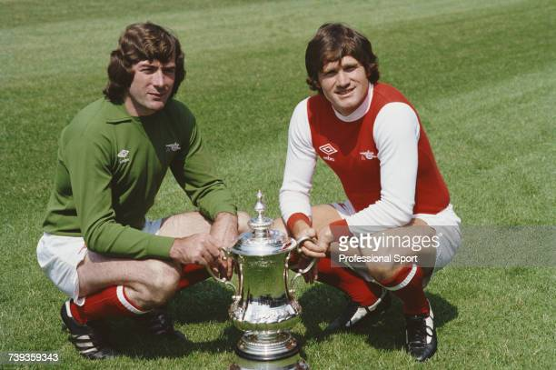 Northern Irish footballers goalkeeper and captain with Arsenal respectively Pat Jennings and Pat Rice pictured posing with the FA Cup trophy on the...