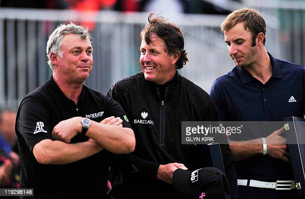 Northern Irish golfer Darren Clarke folds his arms as he stands next US golfer Phil Mickelson and US golfer Dustin Johnson after winning the 140th...