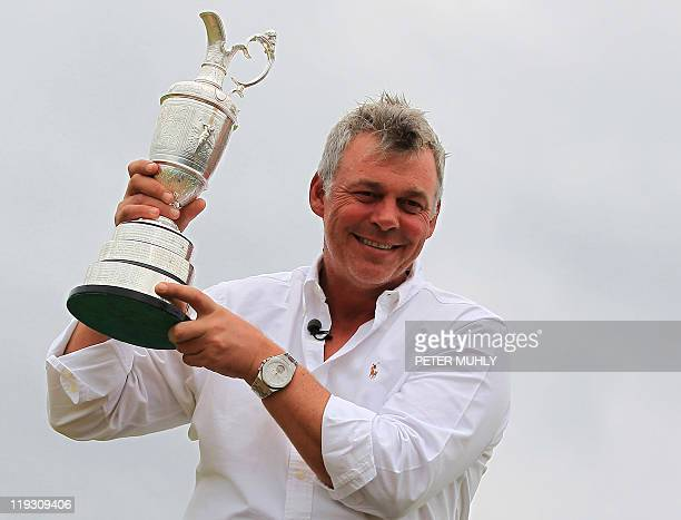 Northern Irish golfer Darren Clarke poses for pictures with the Claret Jug on the 18th green the morning after winning the 140th British Open Golf...