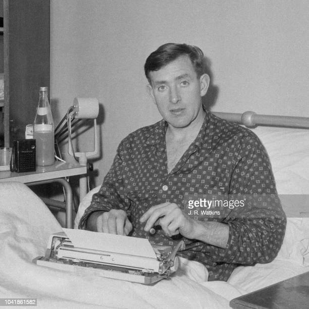 Northern Irish professional footballer and midfielder with Tottenham Hotspur Danny Blanchflower pictured typing on a typewriter in a hospital bed as...