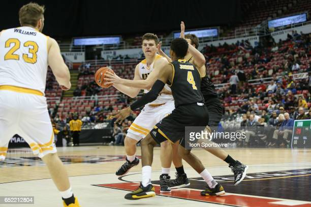 Northern Kentucky Norse forward Drew McDonald looks to pass the ball while being defended by Milwaukee Panthers guard Jeremy Johnson during the...