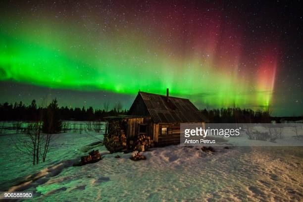 Northern lights above a wooden house
