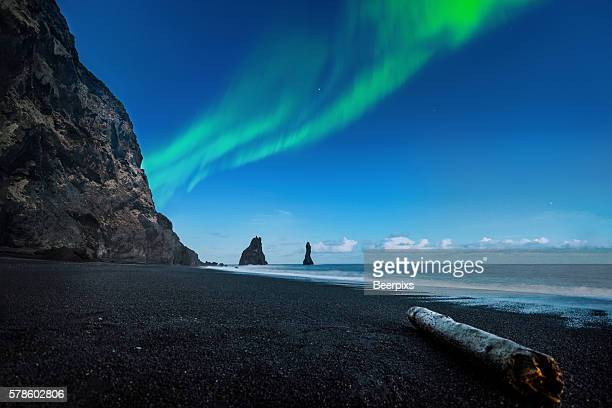 Northern lights above black sand beach near Vik at South coast of Iceland.