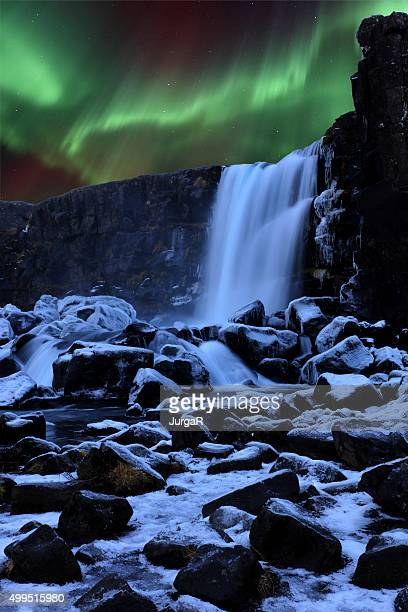 northern lights above oxararfoss waterfall in iceland - pingvellir national park stock photos and pictures