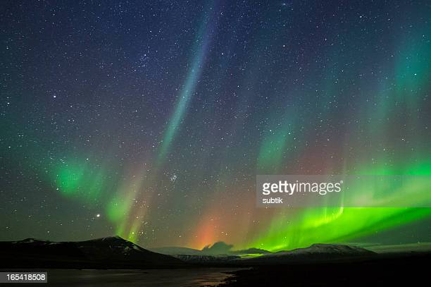 Northern lights against starry sky and silhouette mountains