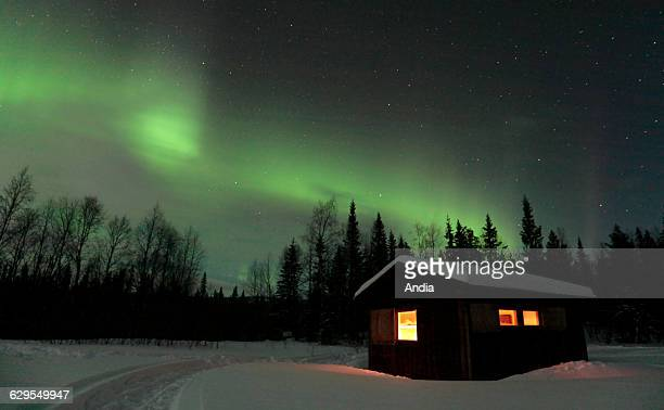 Northern lights and starstudded sky above a hut lit from the inside and snowy landscape at Unna Valle in the area of Partejfallen near the Sarek...